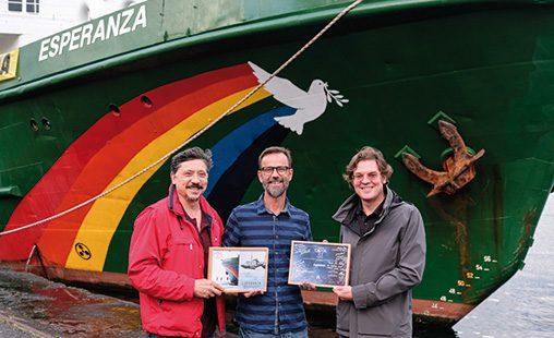 Álvaro Longoria (derecha) y el actor Carlos Bardem (izquierda) hacen entrega al capitán Mike Fimcken (centro) en el barco Esperanza del diploma de nominación en los Goya