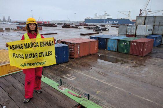 Activista protestando en el puerto de Bilbao con la pancarta 'Armas marca España para matar civiles'