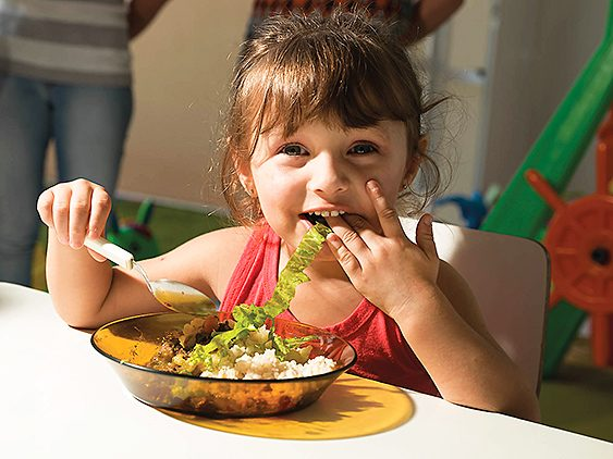 Niña comiendo comida ecológica en el comedor del colegio