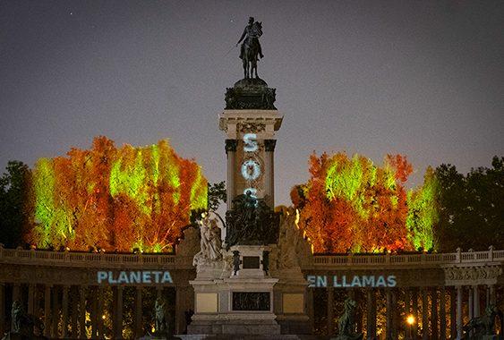 """Activistas de Greenpeace proyectan el mensaje """"SOS. PLANETA EN LLAMAS"""" en los árboles del madrileño Parque del Retiro."""