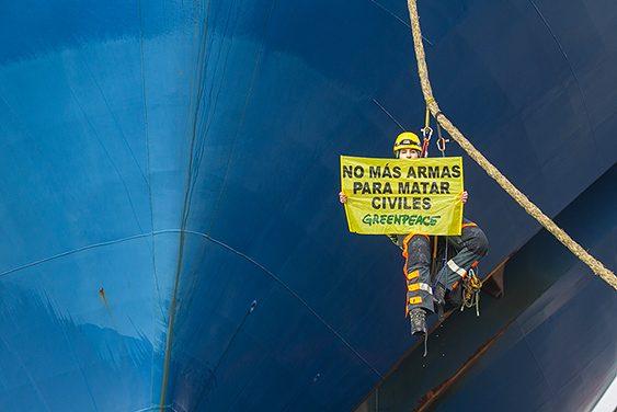 Activista despliega pancarta en uno de los barcos que lleva armas al conflicto