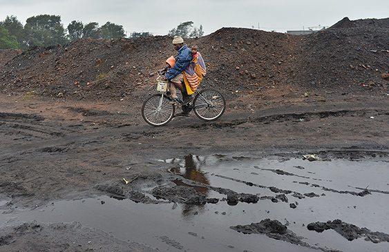 Hombre con sus hijos sobre una bicicleta cruzando tierras contaminadas
