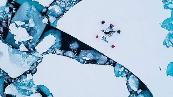 Activistas poniendo pancarta de Greepeace sobre hielo derritiéndose