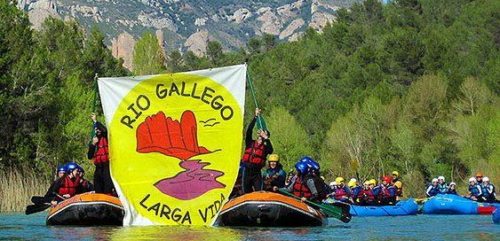 Gente en barca por el río Biscarrues con una pancarta de victoria