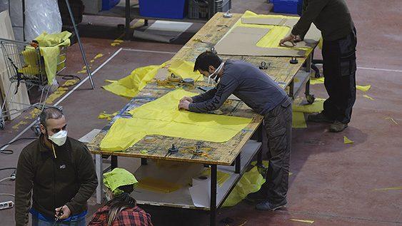 Voluntarios confeccionando batas para los trabajadores de centros de mayores a partir de pancartas de Greenpeace recicladas
