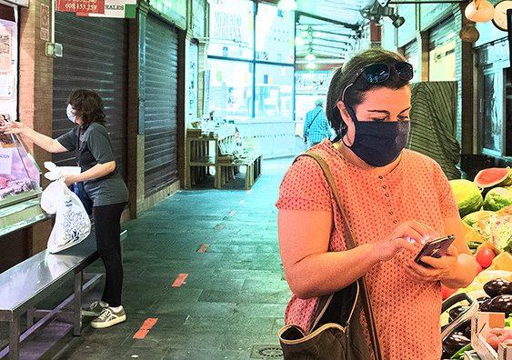 Mujeres comprando en el mercado con las mascarillas puestas
